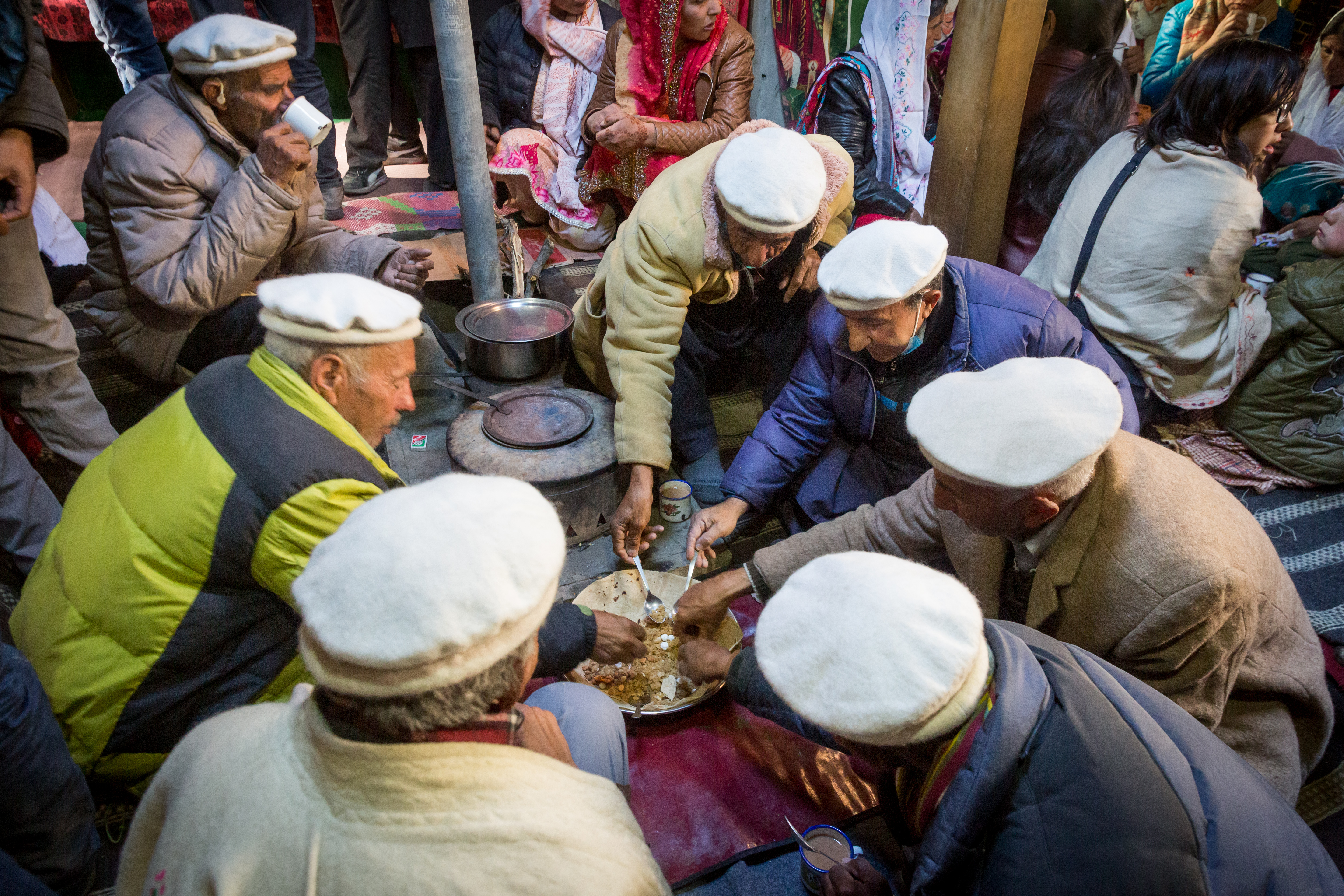 The image shows Wakhi people having meals together in a cultural event. it shows the unity of the Wakhi community and unique cultures in Pakistan